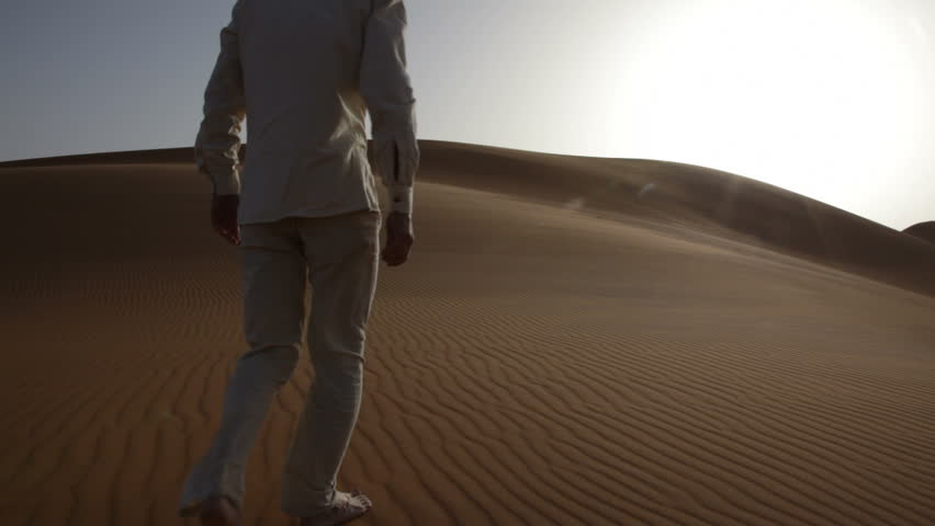Young man walking up sand dunes during a sunny day; Erg Chebbi, Maroc - HD1080p Canon 5Dmk2 - HD stock footage clip