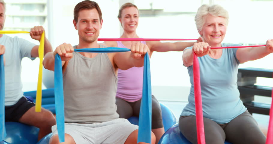 Group sitting on exercise balls stretching resistance bands at the gym