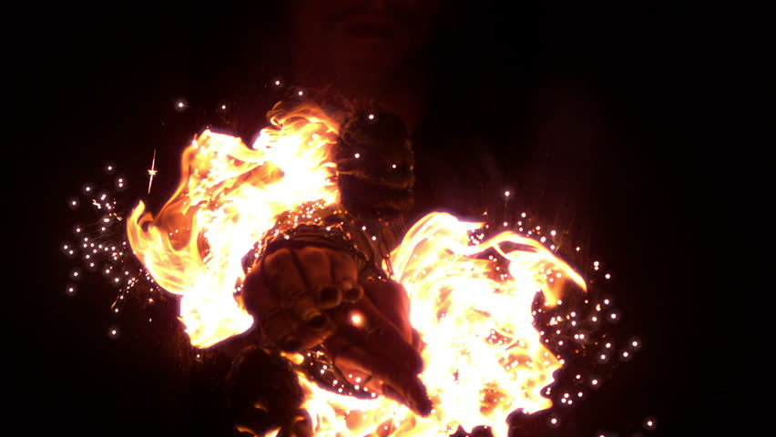 Skilled fire dancer moving in the darkness in slow motion