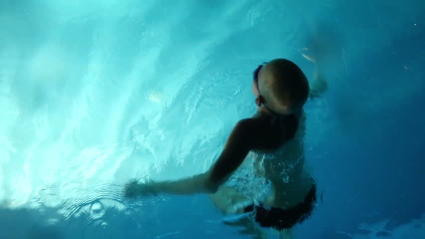 The boy pushed away from the pool edge in swim under water - HD stock footage clip