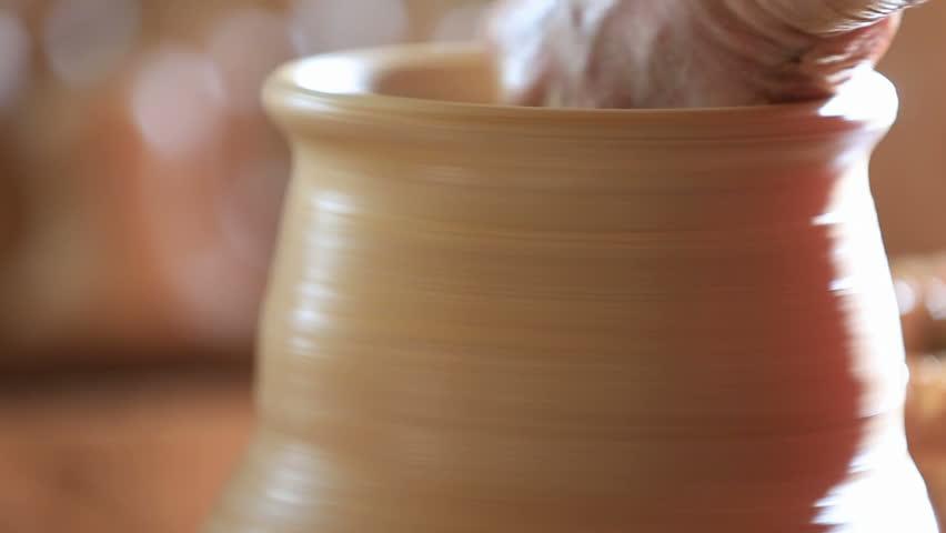 Raising vase on pottery wheel