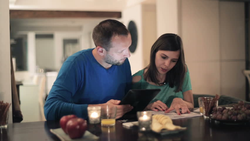 Happy young couple calculating bills by the table at home