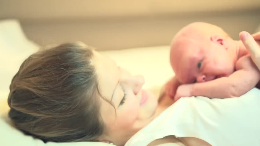 Mother and her Newborn Baby. Happy Mother and Baby kissing and hugging. Resting in bed together. Maternity concept. Parenthood. Motherhood   Beautiful Happy Family Stock Video Footage. Slow Motion