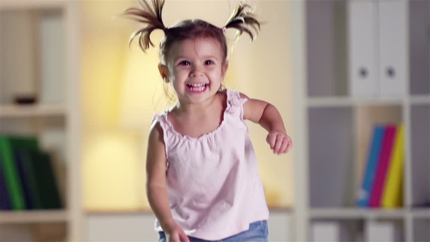 Slow-motion of a cheerful little cutie jumping happily at home
