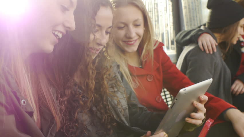 Lens Flare Shot Of Six Teen Girls Waiting At A Station With A Phone And A Tablet