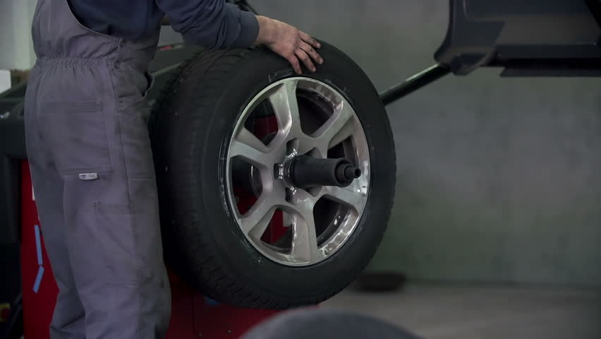 Auto mechanic is checking the precision of tires - HD stock video clip
