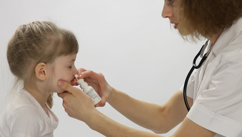 Doctor spraying a nose of a little girl, neutral background