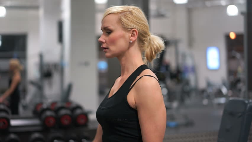 Fit strong young blond woman with toned muscles and biceps in a gym doing a workout, closeup portrait in profile with gym equipment in the background - HD stock video clip