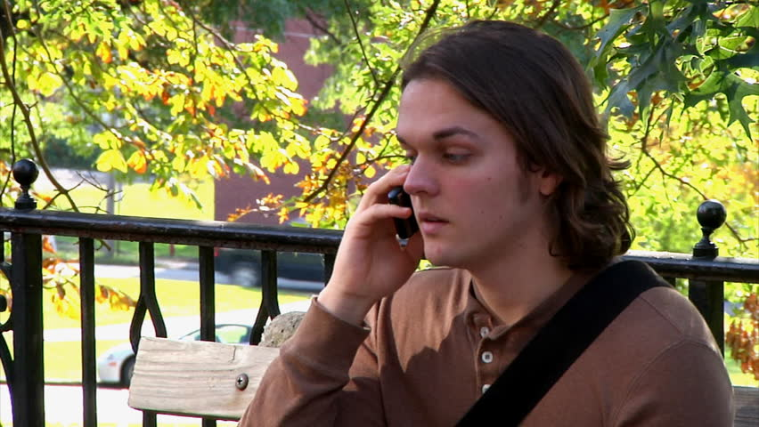 A student talks on his cellular phone on campus. - HD stock footage clip