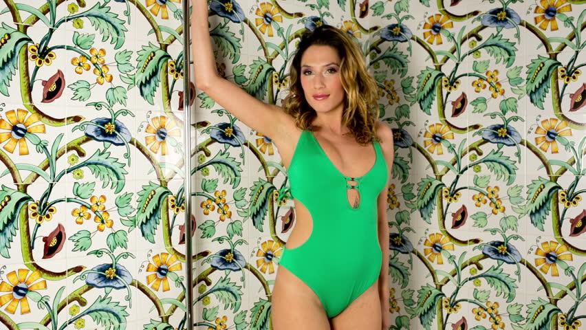 beautiful sexy woman in green bikini whilst posing and dancing in shower  - HD stock footage clip