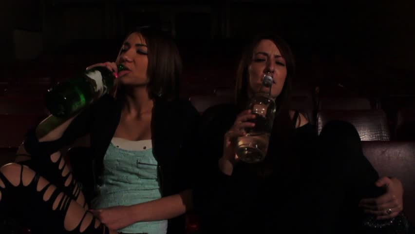 Party time, two young and beautiful girls sitting and drinking whiskey,drunk female holding and knocking the bottles, slow motion shot, interior. - HD stock footage clip