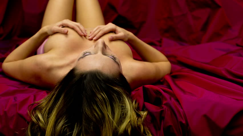 beautiful topless woman moves and poses on a bed.