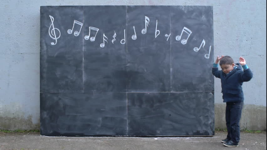 Little Multi-Ethnic Boy Hops R->L Underneath Chalkboard Musical Notes