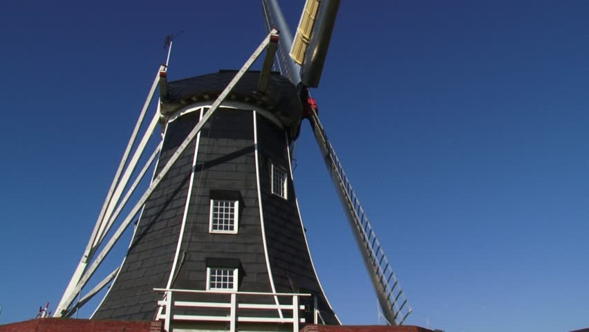 Black tarred windmill - Side view. The beltmolen-type windmill Bataaf dates from 1801 and has been used for milling grain for more than 150 years. WINTERSWIJK, THE NETHERLANDS    - HD stock video clip