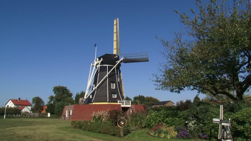 Black tarred beltmolen-type windmill in operation - Side view + scale model windmill in garden. WINTERSWIJK, THE NETHERLANDS  - HD stock footage clip