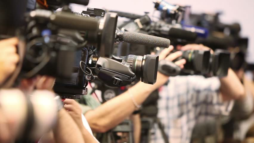 Several video operators with camcorders on tripods recording video at an event