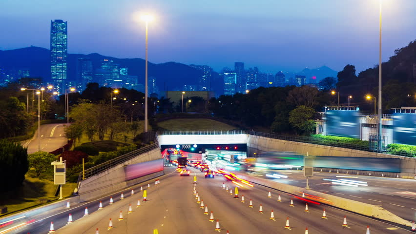 Sunset Busy Traffic Going Into Tunnel. Tight Zoom In Shot. Hong Kong rush hour sunset timelapse. Commercial Office Buildings with commercial billboards. Busy cars entering the cross harbor tunnel. | Shutterstock HD Video #5538536