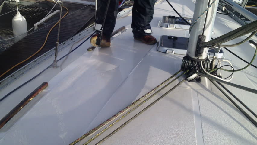 Cleaning the decks of a fibreglass sailing yacht with a jet wash.