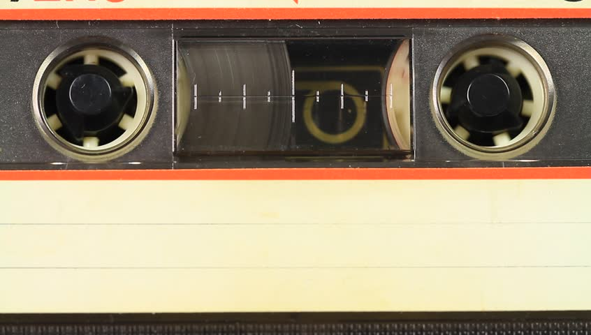 Audio cassette playing. Inserting cassette tape with a blank white label in use playing back in the tape recorder.