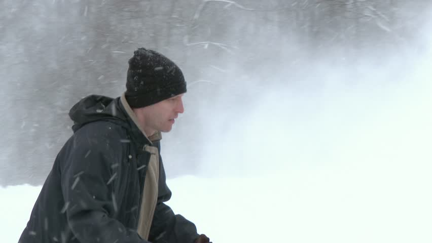 A man clears his driveway with a snow blower.