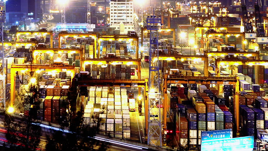 Containers Port Timelapse at Night. Hong Kong. Tight Shot. Cargo containers loading activities in cargo terminal.  Busy traffic across the main road at rush hour. Corporate buildings at the back. - HD stock footage clip