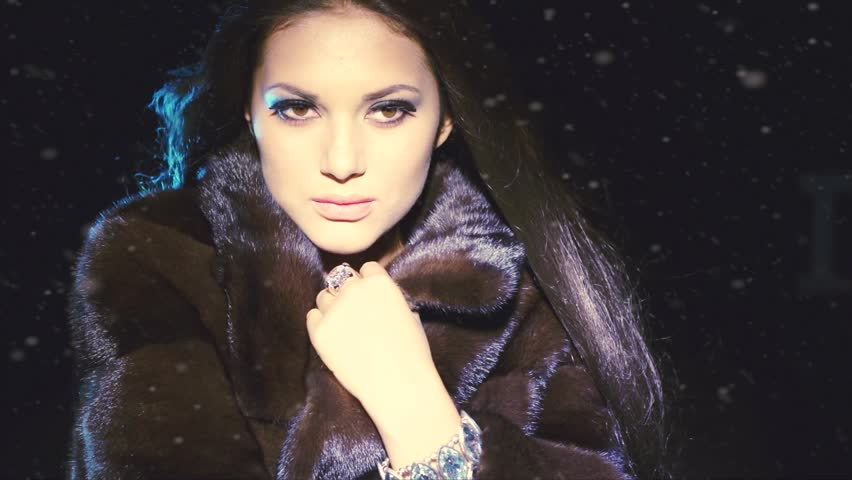 Beauty Fashion Model Girl in Mink Fur Coat. Beautiful Woman in Luxury Black Fur Jacket. Winter Fashion, Blowing Hair in the snow. Over black background. 1920x1080 HD video footage | Shutterstock HD Video #5605424