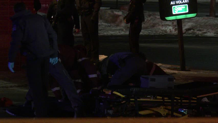 MONTREAL, QC - JAN 2014 - 4K UHD - Ambulance crews strapping patient on stretcher. Ambulance staff is working intensively on getting a victim on a stretcher while doing CPR chest compressions.