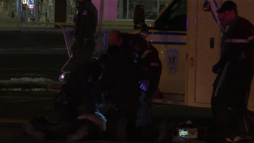MONTREAL, QC - JAN 2014 - 4K UHD - Worked up officers attending shooting victim. Two police officers are taking turn at chest compression CPR on a victim of a gunshot whith paramedics in background.