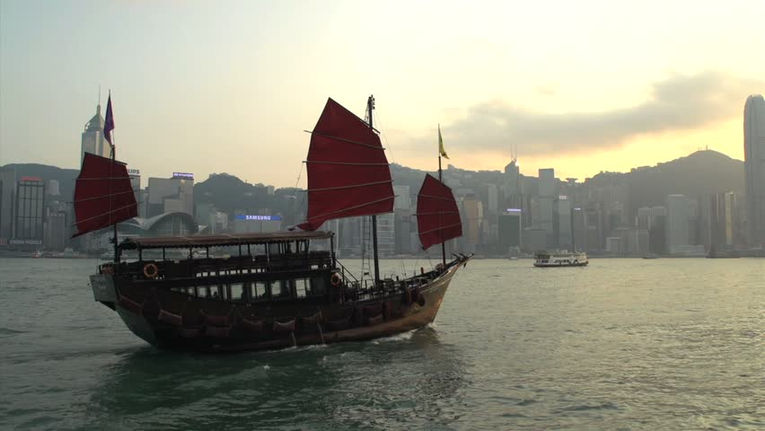 Junk ship in front of Hong Kong skyline during sunset | Shutterstock HD Video #5611580