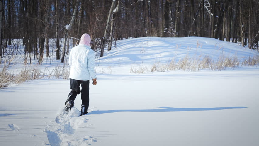 Lonely Woman Snowshoeing in Nature on a Beautiful Winter Day