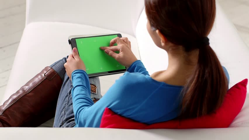 Young people and technology, portrait of beautiful asian girl using tablet pc with green screen, sitting on sofa at home
