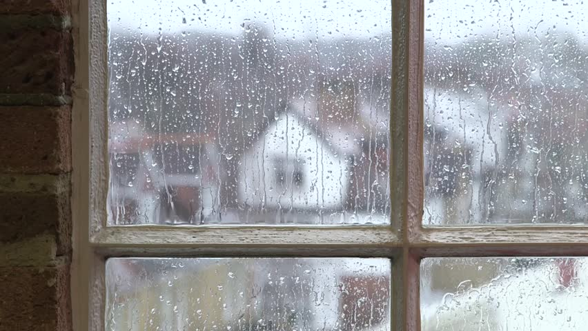 Heavy rain falling against large window pane, raindrops trickle down, grey sky with London houses outside | Shutterstock HD Video #5625494