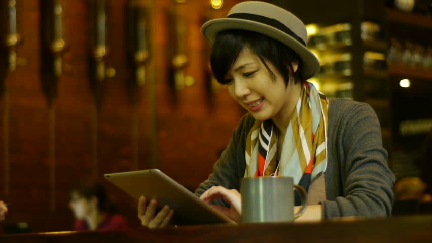 Attractive Young Woman Busy On Her Digital Tablet At A Nice Coffee Shop / Restaurant