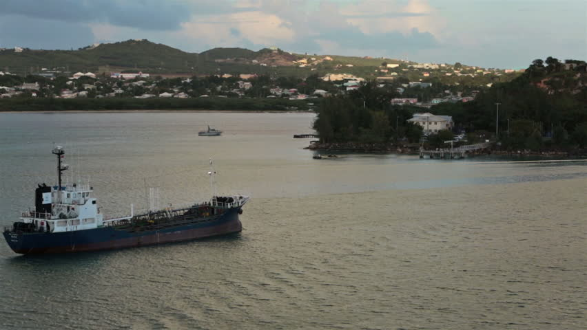 ST JOHNS, ANTIGUA - JAN 2014: Antigua oil fuel ship harbor shoreline sunset. Island imports far more than exports. Poor country rely on tourism for economic stability. Caribbean Ocean. - HD stock video clip