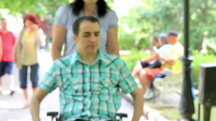Young couple in park. Her husband is in wheelchair. | Shutterstock HD Video #5660324