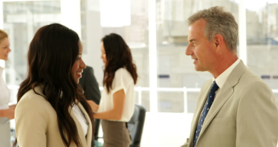 Business people talking together and shaking hands at the office - 4K stock footage clip