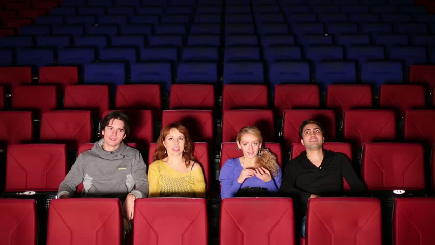 young people sit on their seats in dark hall cinema stock