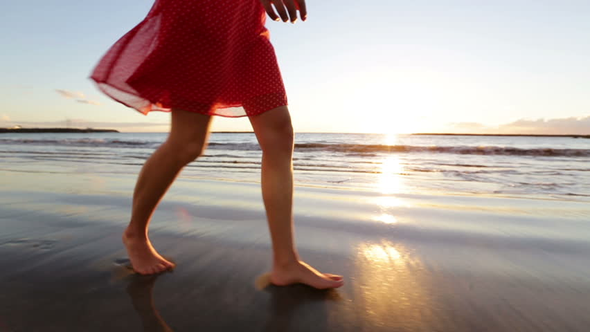 Woman feet and legs walking on beach at sunset. Closeup of beautiful girl in summer dress against the sun flare.