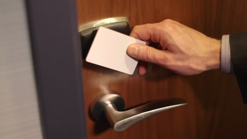 A man in a suit swipes a key card on a secure door and enters the room.