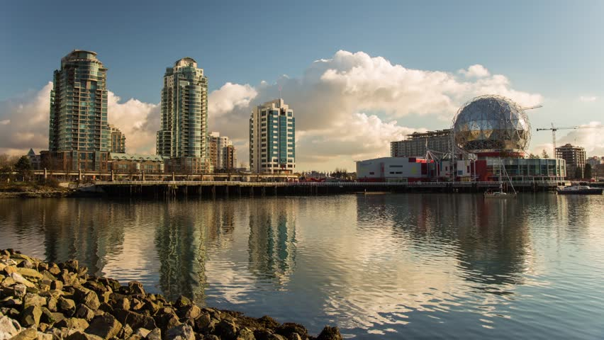 Time lapse of Clouds formation by False Creek Science World in Vancouver with Skytrain passing in the afternoon