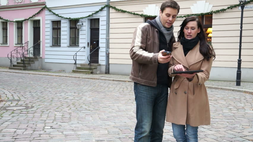 Couple looking for directions on tablet pc and cellphone - HD stock footage clip