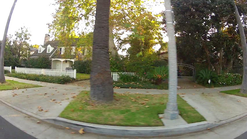 BEVERLY HILLS, CA: February 19, 2014- Side window shot from vehicle of driving by suburban homes circa 2014 in Beverly Hills. Homes illuminated by a sun flare in this exclusive neighborhood. | Shutterstock HD Video #5739335