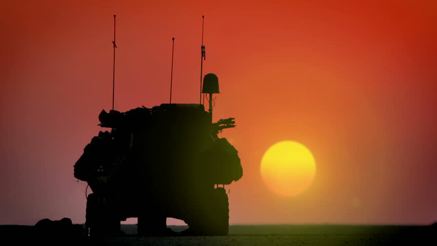 Armored Personnel Carrier (APC) with Apache AH-64 rising in the sunset.