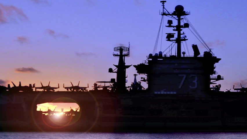 Aircraft carrier silhouette with jet elevator and sunset at sea. Perfect for videos about: aircraft carriers, navy, naval battles, naval craft, ships, carrier groups.