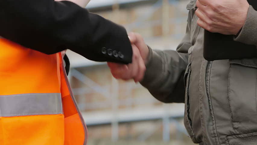Construction people on site. They shake hands. Close up - HD stock footage clip