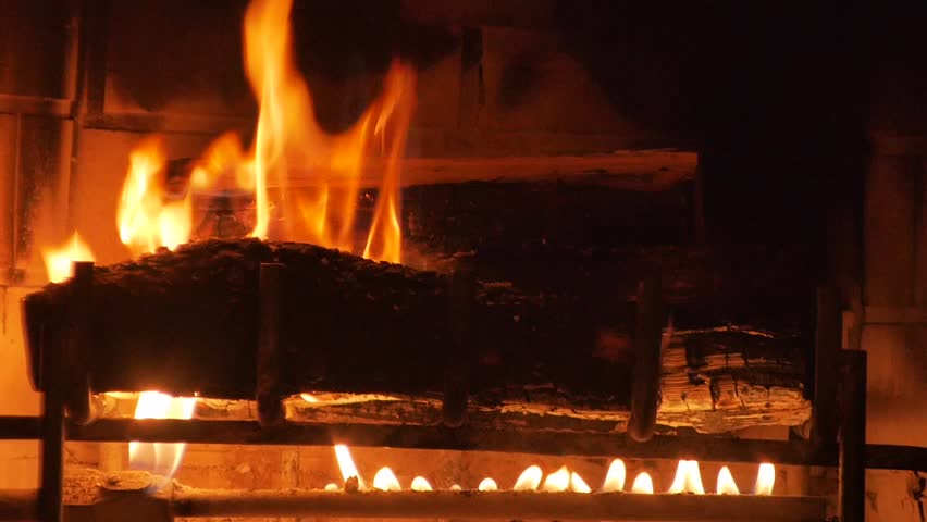 Close up of a yule log burning in a fireplace.