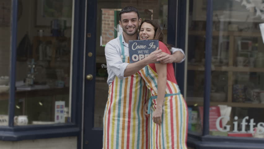 Happy business partners outside a shop hold up a sign to show they are open