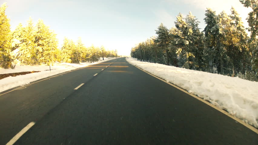 Low angle driving POV on snowy country road in Spain.