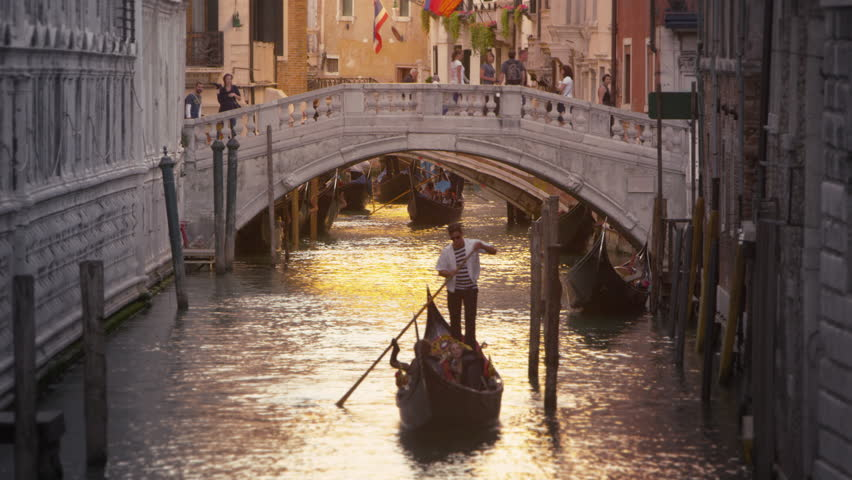 VENICE, ITALY - MAY 3, 2012: Shot of a gondola in a canal with a bridge behind.