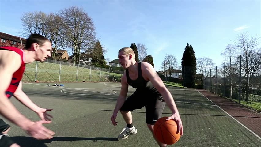 Friends playing basketball outdoors with one player easily defeating the defense and slam dunking - HD stock footage clip